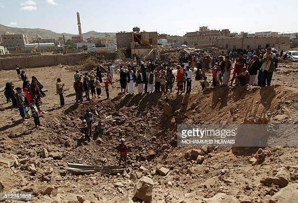 Yemenis look at a hole in the ground following an airstrike by the Saudiled coalition on February 25 2016 in the capital Sanaa / AFP / MOHAMMED HUWAIS