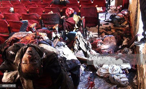 Yemenis look at dead bodies following an attack by a suicide bomber who blew himself up during a celebration by Shiite militia supporters on December...