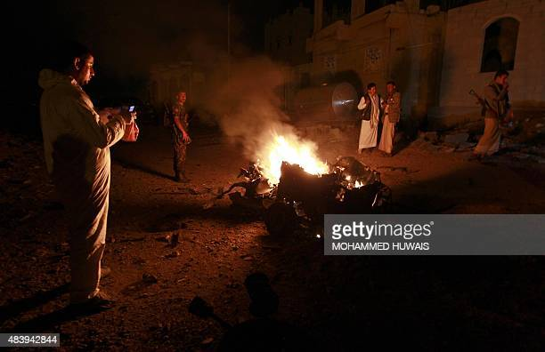 Yemenis look at the wreckage of a vehicle at the site of a car bomb attack in the capital Sanaa late on August 13 2015 AFP PHOTO / MOHAMMED HUWAIS