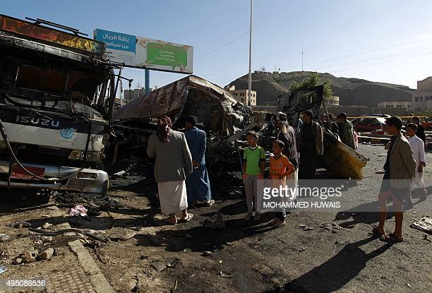 Yemenis look at the wreckage of trucks at the scene of a bomb explosion in Sanaa on October 31 2015 According to reports an improvised explosive...