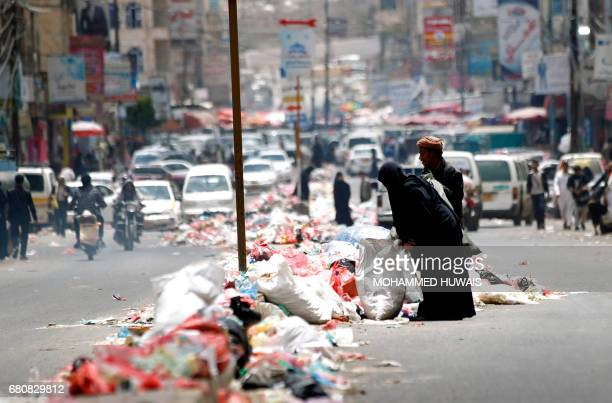 TOPSHOT Yemenis look for items in piles of rubbish lining a road in Sanaa after sanitation workers went on strike over weeks of unpaid wages on May 9...