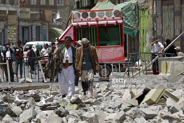 Yemenis make their way through debris following air strikes by the Saudiled coalition on the rebelcontrolled Chief of Staff's headquarters on...