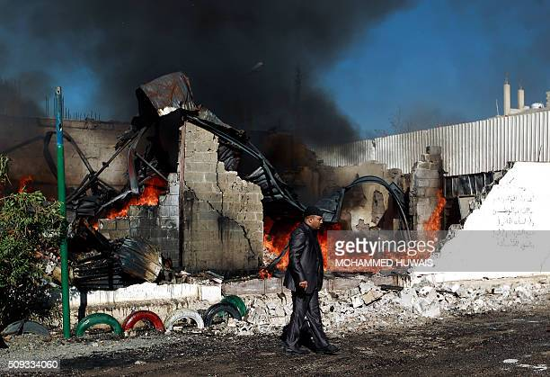 A Yemenis man walks past flames rising from the ruins of buildings destroyed in an airstrike by the Saudiled coalition on February 10 2016 in the...