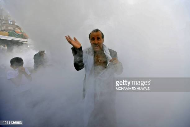 TOPSHOT Yemenis react as municipal workers fumigate a street in the old city market of the capital Sanaa with a disinfectant substance against the...