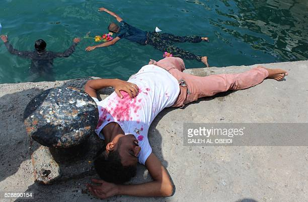 TOPSHOT Yemenis reenact on May 7 2016 the aftermath of a shelling that hit and killed civilians who were trying to escape Yemen by sea to flee the...