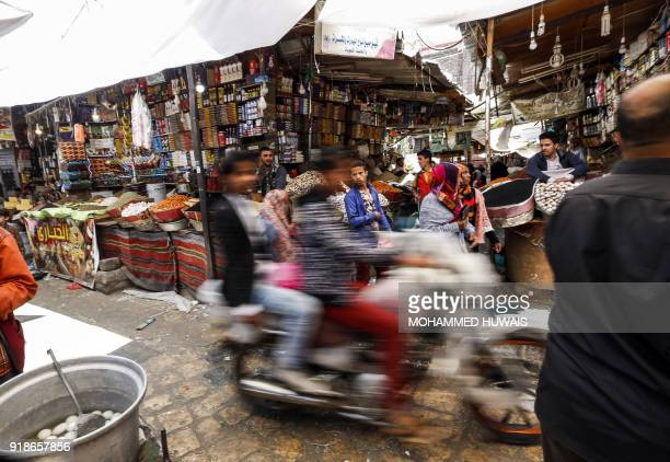 TOPSHOT Yemenis ride in a motorcycle down an alley in the market in the old city of the capital Sanaa on February 15 2018 / AFP PHOTO / MOHAMMED...