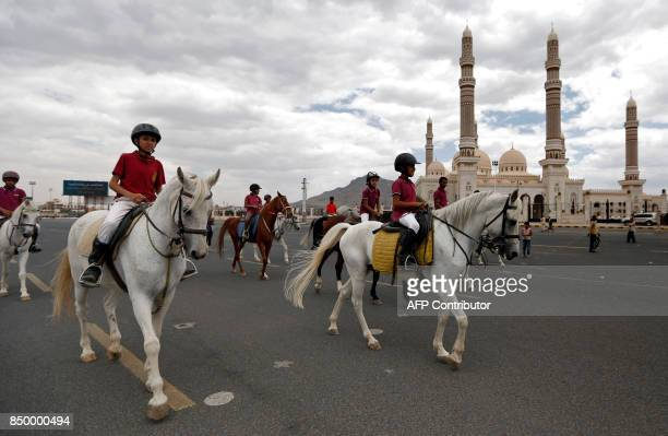 Yemenis rides horses past the AlSaleh mosque in Sanaa as they prepare on the eve of a march to commemorate the third anniversary of the Huthis'...