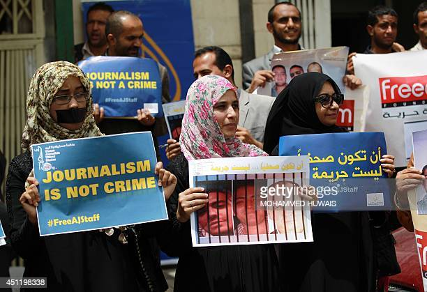 Yemenis some of them being journalists hold placards during a protest on June 25 2014 in the capital Sanaa in solidarity with AlJazeera journalists...