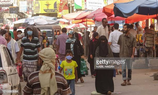Yemenis, some wearing protective mask, shop at a street market in the Crater district of Yemen's southern coastal city of Aden on May 17 amid fears...