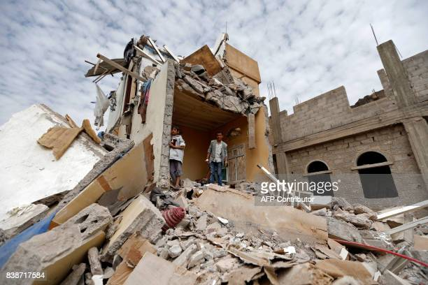TOPSHOT Yemenis stand in the rubble of a house destroyedin an air strike in the residential southern Faj Attan district of the capital Sanaa on...