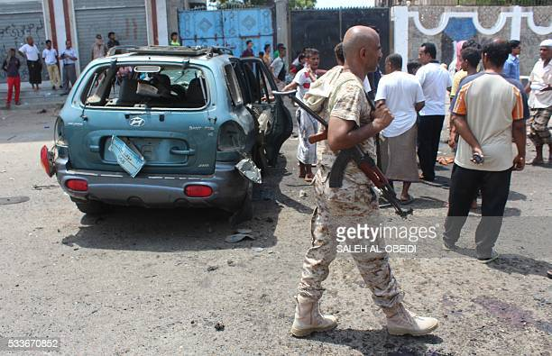 Yemenis stand next to the wreckage of a car at the site of a bombing attack that targeted Yemeni forces in Aden's Khormaksar district on May 23 2016...
