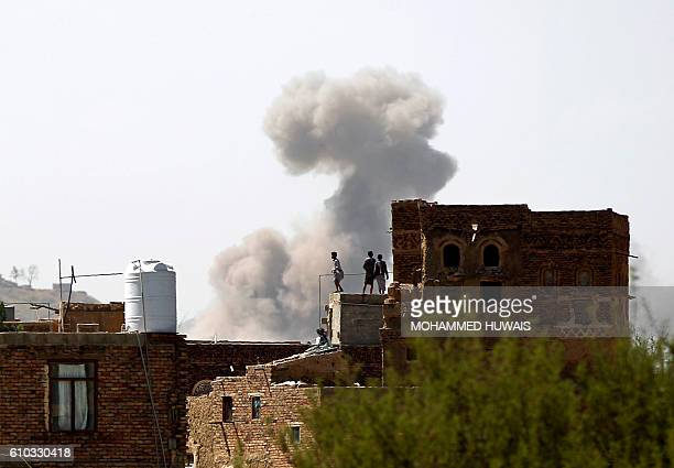Yemenis stand on a rooftop looking at smoke billowing from a building following a reported air strike carried out by the Saudiled coalition in the...