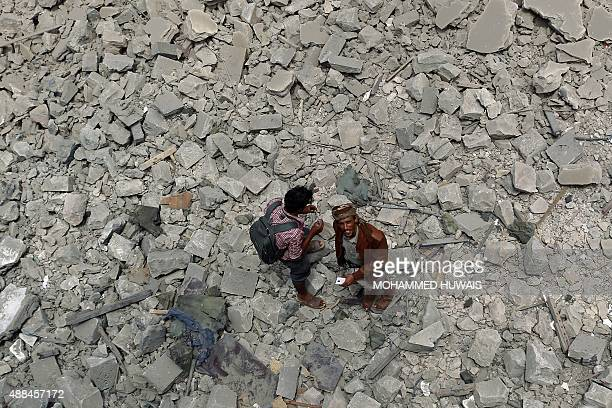 Yemenis stand on the rubble following air strikes by the Saudiled coalition on the rebelcontrolled Chief of Staff's headquarters on September 16 2015...