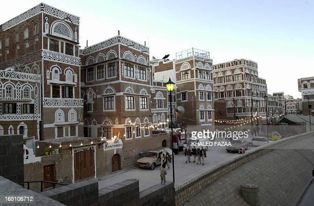 Yemenis stroll in a decorated street in the old quarter of Sanaa 01 January 2004. Sanaa is the Arab cultural capital for 2004 during which a large...