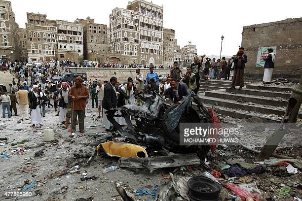 Yemenis surround the wreckage of a vehicle outside the Kobbat alMehdi Shiite mosque in the capital Sanaa on June 20 after a car bomb targeting the...