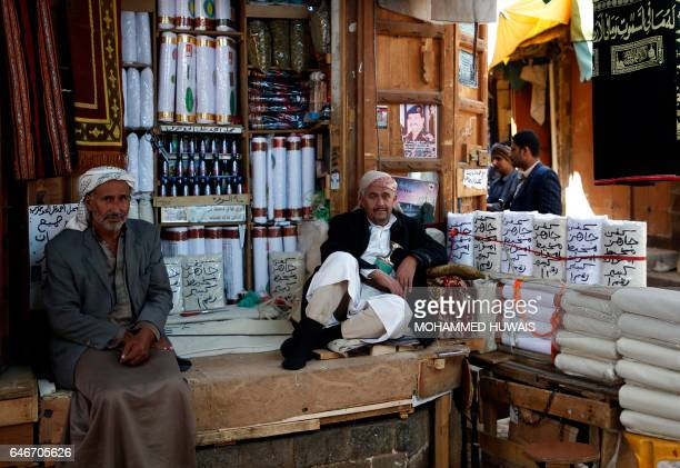 Yemenis vendors sit at a shop in the old city of Sanaa on March 1 2017 / AFP / Mohammed HUWAIS