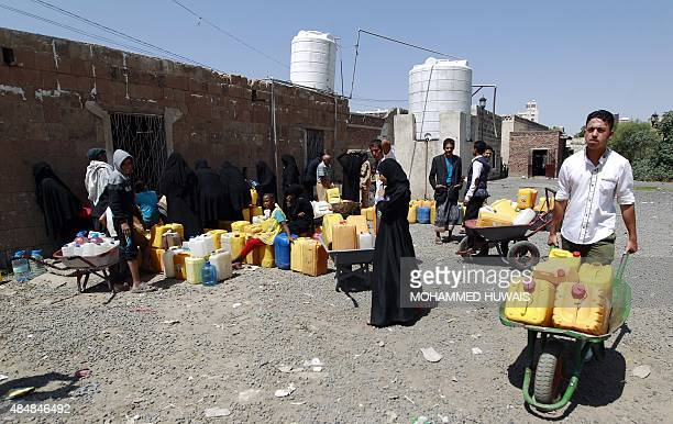 Yemenis wait to fill jerrycans with water from a public tap amid an acute shortage of water supply to houses in the capital Sanaa on August 22, 2015....