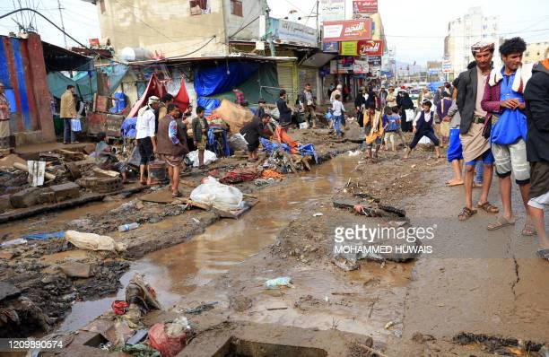 Yemenis walk around a large crack in a damaged road due to floods following heavy rains in the capital Sanaa, on April 14, 2020.