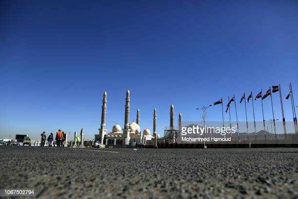 Yemenis walk near alSaleh mosque which renamed recently by the Houthis to alSha'ab mosque at alSabeen square hit by airstrike of warplanes of the...
