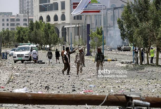 Yemenis walk on a damaged street following a raid by Saudiled coalition warplanes on a nearby missile depot on Fajj Attan hill in the rebelheld part...