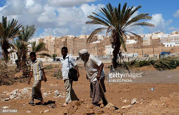 Yemenis walk on the wet earth on the outskirts of the historical city of Shibam in Hadramaut province of eastern Yemen on October 28 following last...