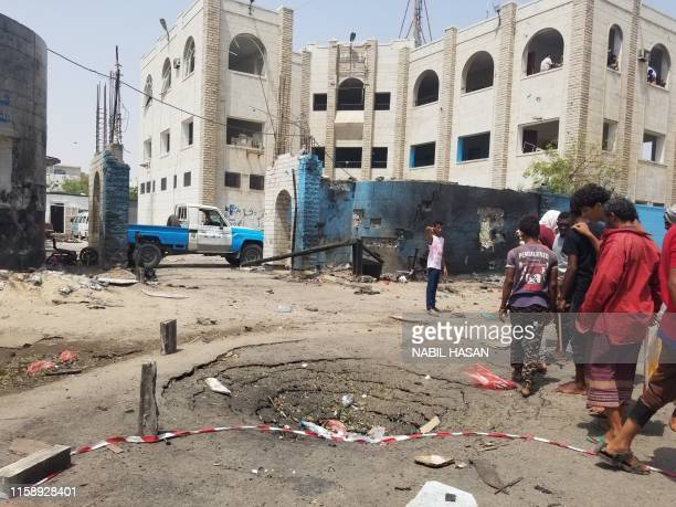 Yemenis walk past a crater at the site of a suicide car bombing on a police station in Sheikh Othman district, in Yemen's government-held second city...
