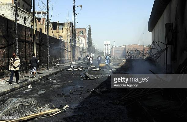 Yemenis walk past a damaged school after war crafts belonging to the Saudiled coalition carried out an airstrike at Musbahi district in Sanaa Yemen...