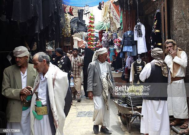 Yemenis walk past stalls at a market in the capital Sanaa's old city on July 27 2015 Warplanes from the Saudiled coalition fighting Iranbacked rebels...