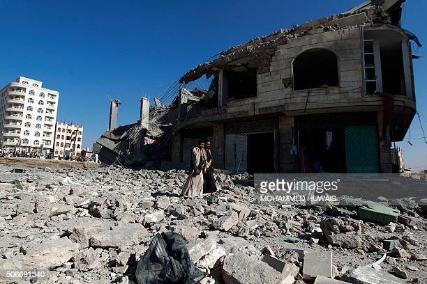 Yemenis walk past the site of a Saudiled airstrike that targeted a building in the Yemeni capital Sanaa on January 25 2016 A Saudiled coalition...