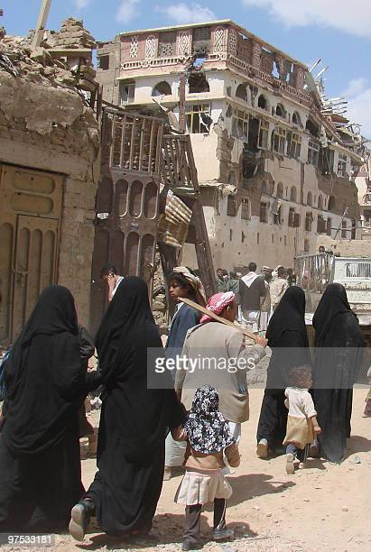 Yemenis walk through a heavily damaged neighbourhood in the warbattered city of Saada 240 kms north of the Yemeni capital Sanaa on March 8 one month...