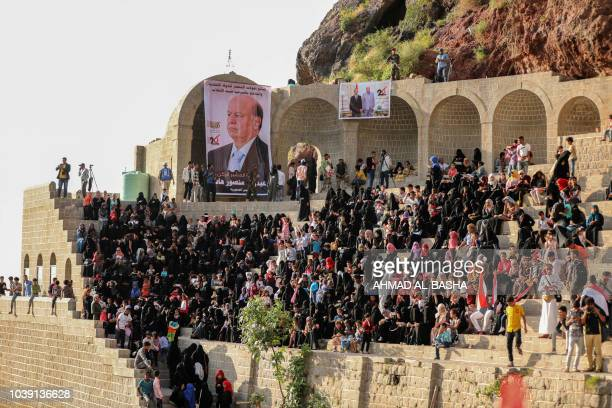Yemenis wave national flags and stand near a banner showing the picture of Saudibacked President Abedrabbo Mansour Hadi during a celebration marking...