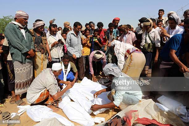 Yemenis wrap in shrouds the bodies of members of the same family during their funeral on October 8 a day after they were killed in a reported...