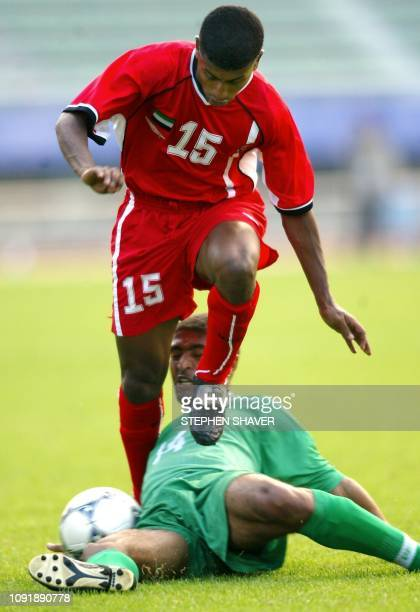 Yemen's Ahmed Salem Ahmed Al Zuraial slide tackles United Arab Emirates' Fahed Masoud Ali Masoud during their football match 30 September 2002 at the...