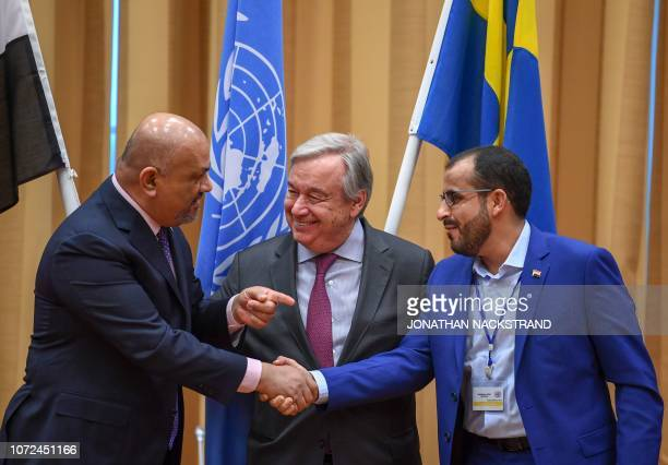 TOPSHOT Yemen's foreign minister Khaled alYamani and rebel negotiator Mohammed Abdelsalam shake hands under the eyes of United Nations Secretary...