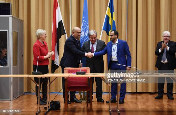 Yemen's foreign minister Khaled alYamani and rebel negotiator Mohammed Abdelsalam shake hands under the eyes of United Nations Secretary General...