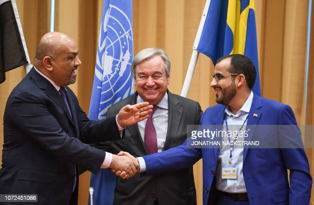Yemen's foreign minister Khaled alYamani and the head orebel negotiator Mohammed Abdelsalam shake hands under the eyes of United Nations Secretary...
