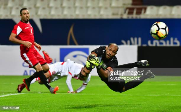 Yemen's goalkeeper and captain Mohammed Ayash leaps to save the ball after it was kicked by Bahrain's forward Mahdi Abduljabbar and Yemeni defender...