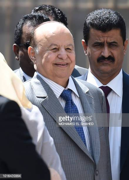 Yemen's internationally recognised government President Abedrabbo Mansour Hadi smiles as he walks with Arab League SecretaryGeneral during their...