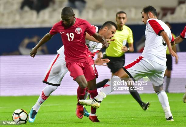 Yemen's Mohammed Fuad Mohammed Omar vies for the ball with Qatar's Almoez Ali during their 2017 Gulf Cup of Nations football match between Qatar and...