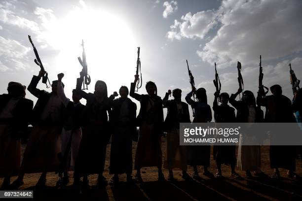 TOPSHOT Yemen's Shiite Huthi rebels shout slogans during a gathering to mobilise more fighters to battlefronts to fight progovernment forces on June...