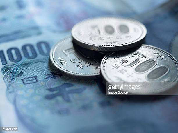 yen coins and banknotes - japanese yen note stock photos and pictures