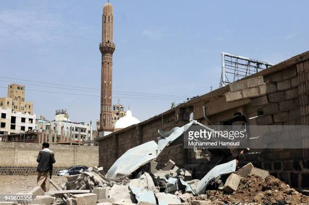 Yeneni people are seen at a power station after it was hit by aitstrikes of the Saudiled coalition on April 20 2018 in Sana'a Yemen
