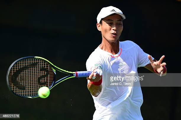 Yen-Hsun Lu of Chinese Taipei returns a shot from Guillermo Garcia-Lopez of Spain during the second day of the Winston-Salem Open at Wake Forest...