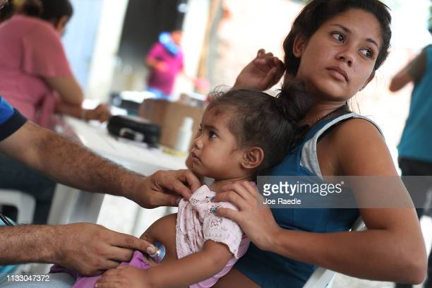 Yenire Quintero holds her baby Yendrimar Figueroa as Dr Ardenis Mena checks on her baby at a the VENCUC health care clinic setup near the border on...