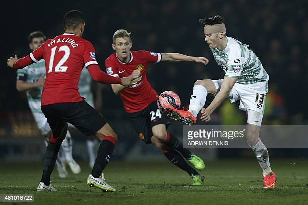 Yeovil Town's English striker Kieffer Moore controls the ball under pressure from Manchester United's English defender Chris Smalling and Manchester...
