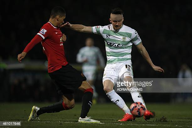 Yeovil Town's English striker Kieffer Moore has a shot at goal which is deflected by Manchester United's English defender Chris Smalling during the...