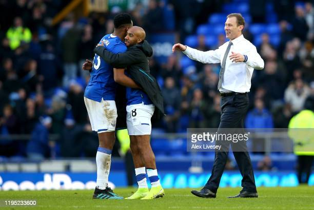 Yerry Mina and Fabian Delph of Everton embrace as Interim Everton Manager Duncan Ferguson looks on after the Premier League match between Everton FC...