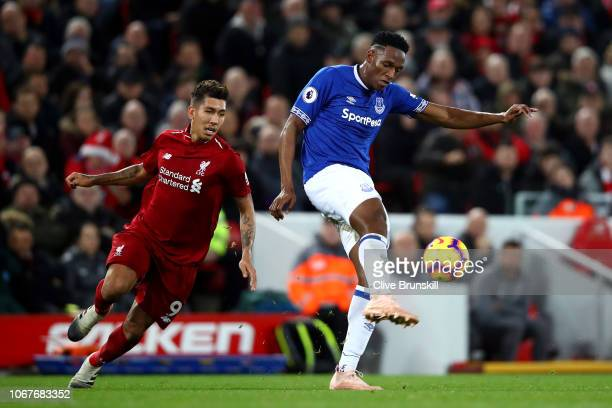 Yerry Mina of Everton clears the ball under pressure from Roberto Firmino of Liverpool during the Premier League match between Liverpool FC and...