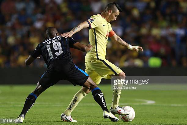 Yerson Candelo of Queretaro struggles for the ball with Rubens Sambueza of America during the 14th round match between Queretaro and America as part...