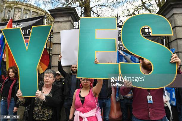 'Yes' vote campaigners cover antiabortion group's graphic images related to pregnancy and abortion with Irish and rainbow flags and white billboards...